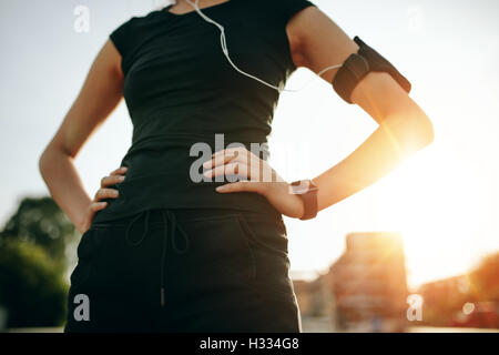 Cropped shot of fit young woman standing with her hands on hips. Urban runner outdoors in sunny morning. - Stock Photo