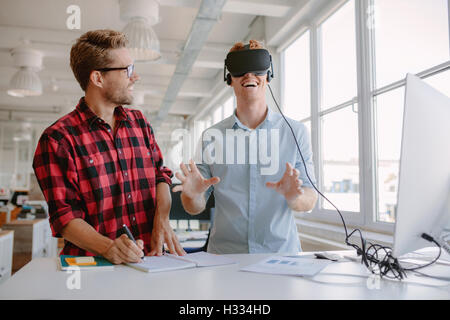 Shot of two young men testing virtual reality glasses in office. Businessman wearing VR goggles and colleague writing - Stock Photo