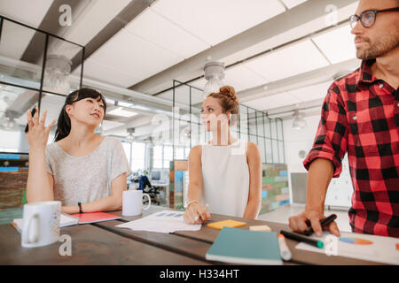Group of multiracial coworkers discussing new business ideas around a table in creative office. - Stock Photo