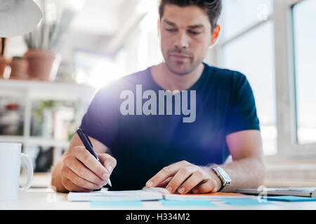 Young male business executive writing down some important notes in diary at his desk. Young businessman updating - Stock Photo