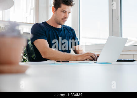 Busy young man working on laptop computer in office. Young male executive using laptop at his desk. - Stock Photo