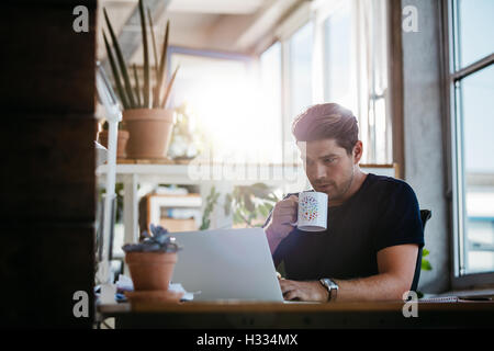 Young business man sitting at his desk working on laptop and drinking coffee. Young man in modern workplace surfing - Stock Photo
