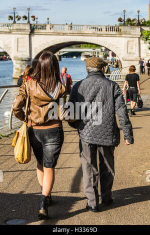 A young woman walks with her father near the River Thames in Kingston-Upon-Thames in Surrey, England, UK - Stock Photo
