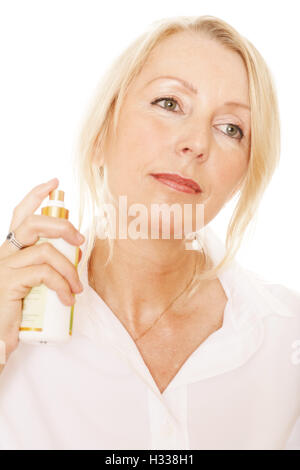 Woman, 49, spraying herself with a perfume bottle - Stock Photo