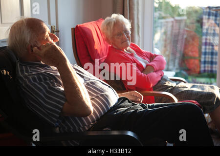 Elderly couple sat inside enjoying the afternoon sun which is shining through the windows of their home, Southwest - Stock Photo