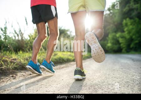 Unrecognizable senior couple running outside in sunny nature - Stock Photo
