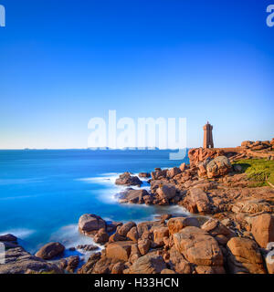 Ploumanach Mean Ruz lighthouse red sunset in pink granite coast, Perros Guirec, Brittany, France. Long exposure. - Stock Photo