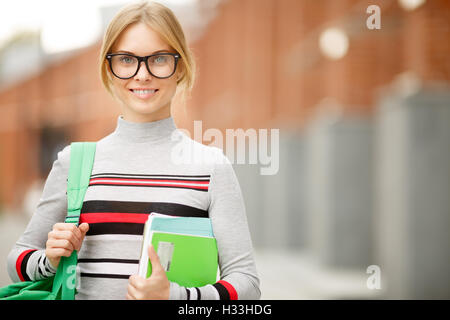 girl in glasses close-up against backdrop of buildings - Stock Photo