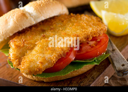 A delicious homemade fish burger with lettuce and tomato on a bun. - Stock Photo