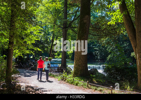 Couple by the Eisbach in the Englischer Garten, Munich, Bavaria, Germany - Stock Photo