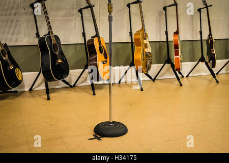 X marks the spot on floor where Elvis Presley recorded hit songs at Sun Record Studios with Guitars lining the wall - Stock Photo