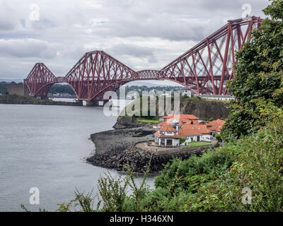 Homes under the Forth Rail Bridge in Edinburgh, Scotland, connecting the towns of North and South - Stock Photo