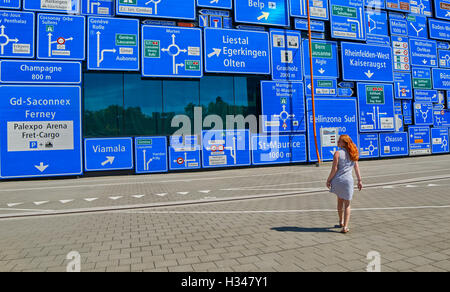Woman lost her way against a wall with a lot of road signs - Stock Photo
