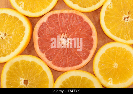 Orange and grapefruit slices on wooden butting board. - Stock Photo