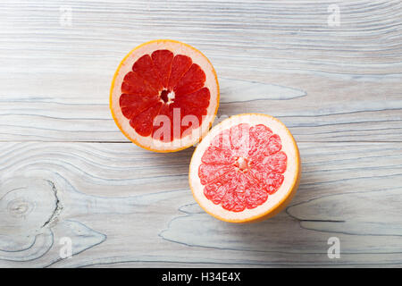 Sliced fresh ripe grapefruit over white natural aged wooden background - Stock Photo