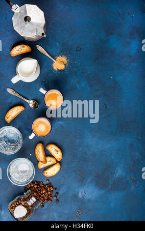 Coffee espresso, cantucci, cookies and milk over dark blue background - Stock Photo
