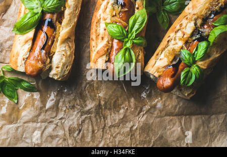 Homemade grilled sausage dogs in baguette on baking paper - Stock Photo