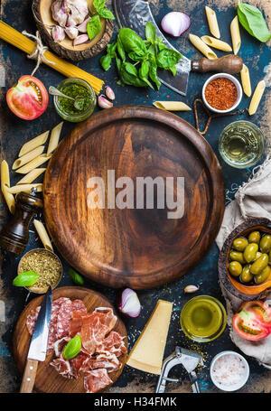 Italian food cooking ingredients on dark plywood background, copy space
