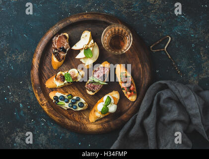Italian crostini and glass of wine on round serving tray - Stock Photo
