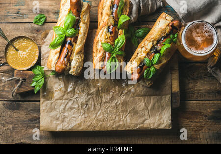 Glasses of wheat unfiltered beer and homemade grilled sausage dogs - Stock Photo