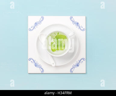 Cup of tea on white tile board over sky-blue background - Stock Photo