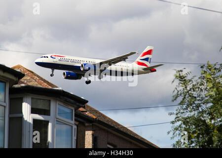 British Airways Airbus A320-232 over houses near Heathrow Airport - Stock Photo