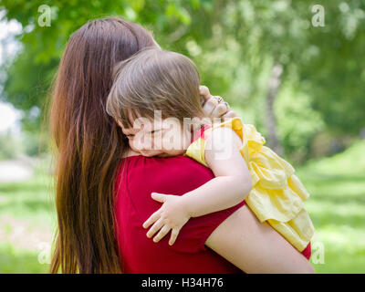 Mother holding crying baby girl with tears - Stock Photo