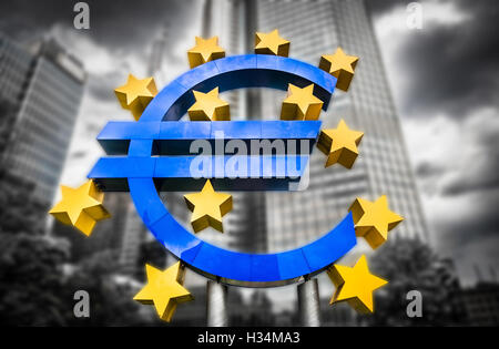 Euro sign at European Central Bank headquarters in Frankfurt, Germany on abstract blurred background of dramatic - Stock Photo