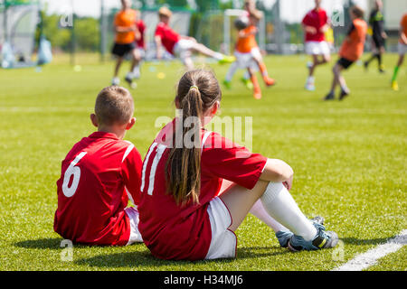 Children soccer players playing game. Young girl and boy soccer players sitting together on grass football field - Stock Photo