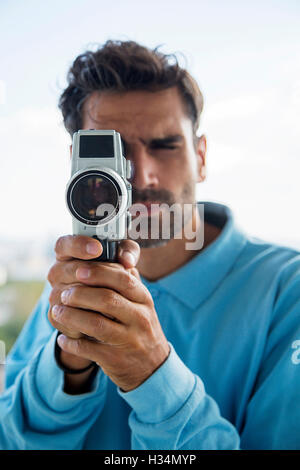 Handsome young man with old fashioned camera - Stock Photo