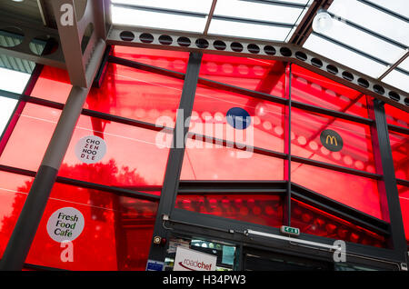 Red glass panels make a striking feature above the entrance to a Roadchef service station - Stock Photo