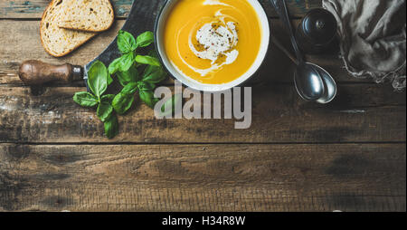 Pumpkin cream soup in bowl with fresh basil and spices - Stock Photo