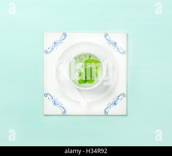 Cup of tea on white tile board over mint background - Stock Photo