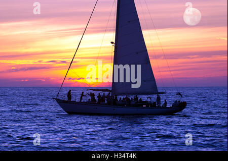 Sailboat sunset is a boat full of people sailing along the ocean water with a vibrant sunset in the background. - Stock Photo