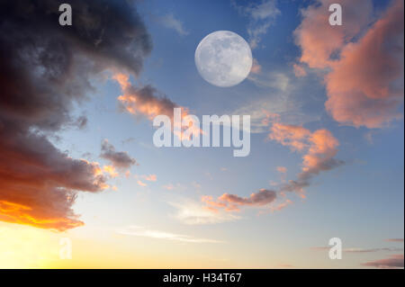 Clouds moon is a vibrant colorful cloudscape at sunset with an ethereal full moon rising in the sky. - Stock Photo