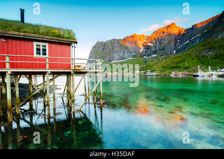 Typical house of fishermen called Rorbu lit up by midnight sun, Reine, Nordland county, Lofoten Islands, Arctic, - Stock Photo