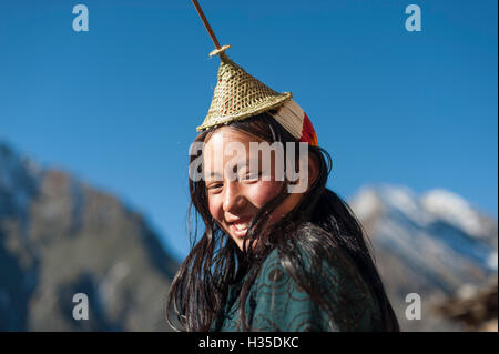 A Layap girl wearing a traditional hat smiles for the camera in the remote village of Laya, Bhutan - Stock Photo