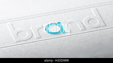 3D illustration of the word brand embossed on a paper background with blur effect. Concept of company brandname - Stock Photo