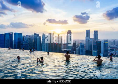 Infinity pool on the roof of the Marina Bay Sands Hotel with spectacular views over the Singapore skyline at sunset, - Stock Photo