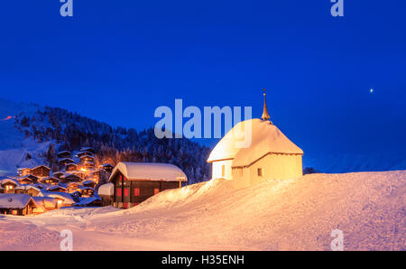 Blue dusk on the alpine village and church covered with snow, Bettmeralp, district of Raron, canton of Valais, Switzerland - Stock Photo