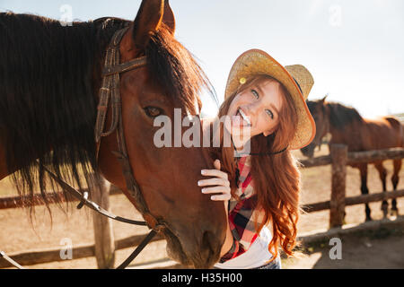 Cheerful playful young woman cowgirl standing with horse and showing tongue - Stock Photo
