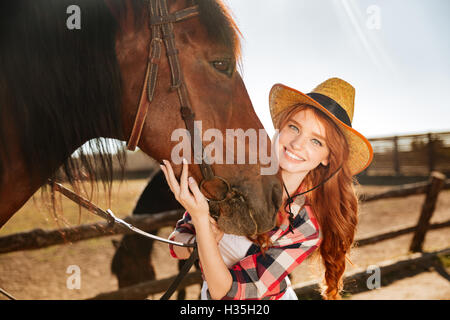 Smiling attractive young woman cowgirl standing with her horse on farm - Stock Photo