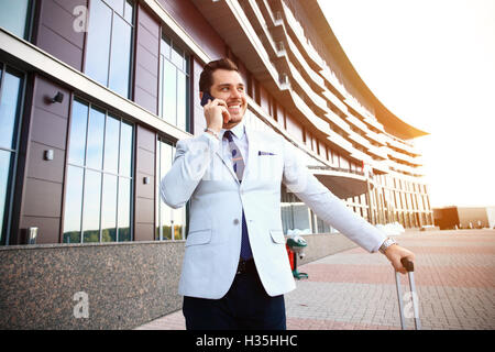Young happy traveler businessman making call after arriving at hotel outside with his luggage. - Stock Photo