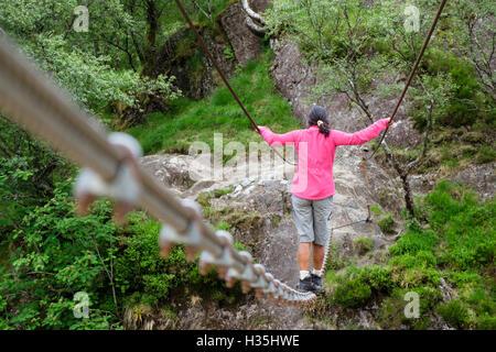 Asian woman in pink walking across Steall wire rope bridge crossing Water of Nevis river. Glen Nevis Fort William - Stock Photo