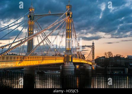 Albert Bridge illuminated at sunset over the river Thames London UK - Stock Photo