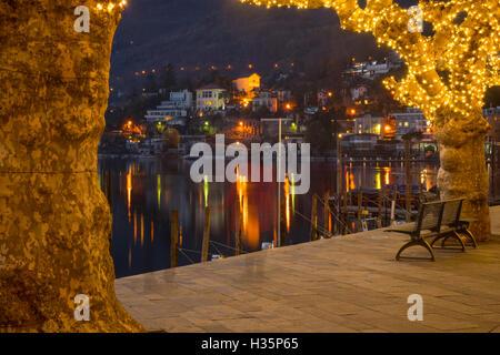 Sunset scene of the lake promenade Piazza Mota, with Christmas decoration, in Ascona, Ticino, Switzerland - Stock Photo