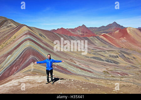 The photographer posing in front of the beautiful colored Rainbow Mountain panorama near Cusco Peru. Nice view into - Stock Photo