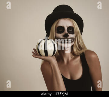 A blond girl is wearing scary skeleton makeup paint on her face. She is holding pumpkin decor for a halloween message - Stock Photo