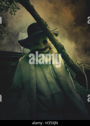 A scary evil scarecrow man is holding a stick with a monster burlap mask on his face for a nightmare halloween concept.