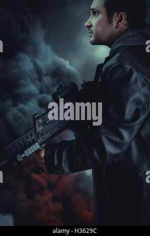 Man with long leather jacket and assault rifle, black smoke background - Stock Photo